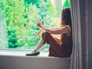 Young woman sitting by the window with phone