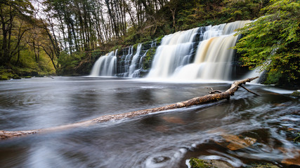 Long exposure of a waterfall (Sgwd Y Pannwr) in a tree covered forest in the autumn