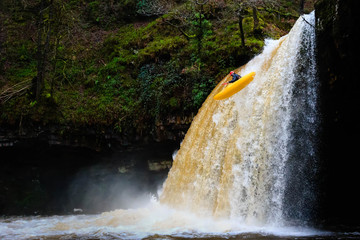 A canoe being paddled off a tall, fast flowing waterfall
