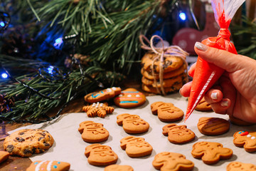 Decoration process of Christmas bakery. Unrecognizable woman garnishing with icing homemade gingerbread cookies near pine branch with festive decor. Family culinary and New Year traditions concept