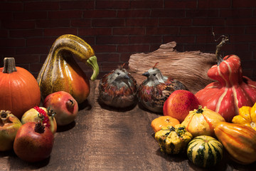 Thanksgiving display with pumpkins, gourds, feather birds, and pomegranates on warm rough wood table against brick wall