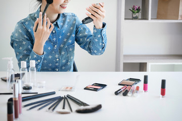 Happy smiling elegant woman or beauty blogger with brush on recording video while review product make up tutorial for theme about video blogging on camera screen