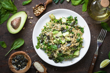 Fresh quinoa salad with spinach, avocado, seeds and Pine nuts. Top view on dark table.