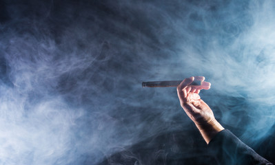 A man holds a cigar in hand, a lot of smoke is visible