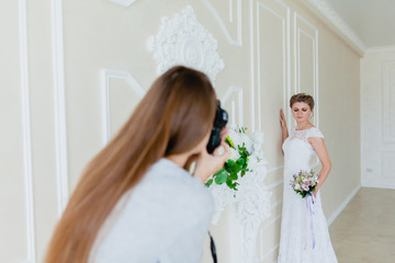 Photographer taking pictures the young sexy bride in the studio