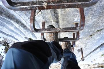 Aufstieg im Klettersteig über in der vertikalen Kalksteinwand angebrachte Stahl-Steighilfen