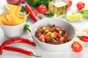 Chili con carne in bowl served with chips on kitchen table