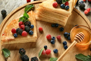 Tasty thin pancakes with berries on wooden board