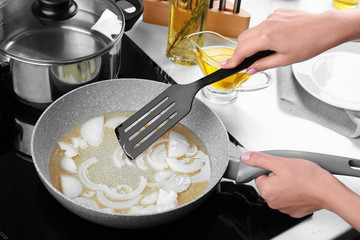 Woman frying onion in kitchen