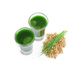 Wheat grass shots and grain on white background