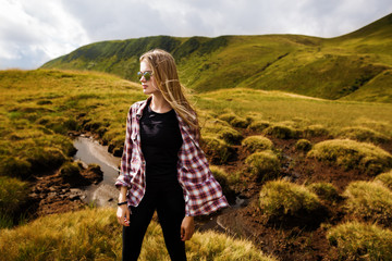Shot of a young woman looking at the landscape while hiking in the mountains. Hipster young girl