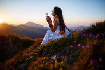 Photo sur Plexiglas Marron chocolat A girl sits on the edge of the cliff and looking at the sun valley and mountains. Woman sitting on mountain top and contemplating the sunset. Young woman in long white dress