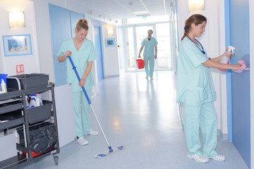 cleaner with mop and uniform cleaning hospitals corridor