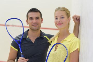 young cheerful couple after playing badminton