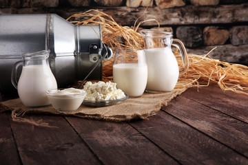 Deurstickers Zuivelproducten milk products. tasty healthy dairy products on a table on. sour cream in a bowl, cottage cheese bowl, cream in a a bank and milk jar, glass bottle and in a glass