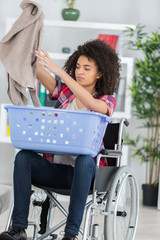 young happy woman on wheelchair putting clothes in basket