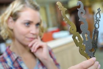 female blacksmith choosing metal finish