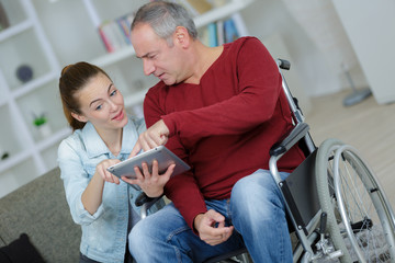 senior using a tablet in a wheelchair in at home