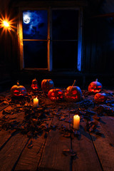 The concept of Halloween. A lot of luminous evil scary pumpkins, jack lantern, with candles, leaves and clouds and a moon outside the window with a warm and cold blue light on the wooden floor