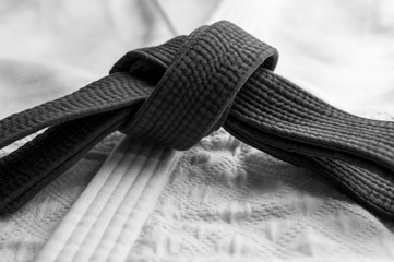 Black judo, aikido or karate belt on white budo gi