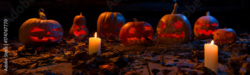 The concept of Halloween. A lot of luminous evil terrible pumpkins, jack-lantern, with candles, leaves with a warm and cold blue light on the wooden floor. Ultra wide photo