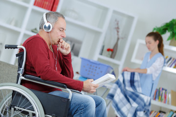 senior man in wheelchair with help of carer