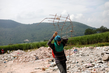 A man carries a twisted iron frame while searching for salvageable items at a site for the rubble of buildings damaged in the earthquake on the outskirts of Jojutla de Juarez