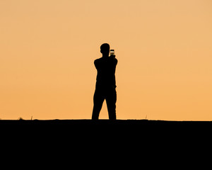 A man taking selfie on sunset
