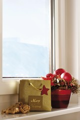 Lying Putte, and a Christmas bag and arrangement on a windowsill