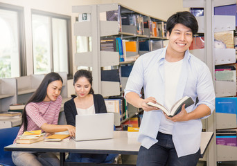 Portrait of asian man with two asian college students using laptop in the library, asian man and woman reading book and study in the library.