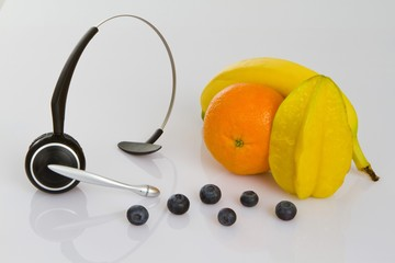 Headphones with a clementine, star fruit or carambola, banana and blueberries as a symbol for healthy eating at work
