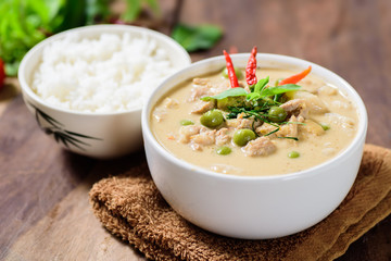 Thai food (Panaeng curry),red curry with pork and cooked rice in a bowl on wooden background