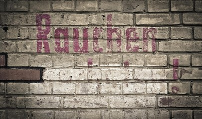 "Brick wall with the word ""Rauchen"", German for ""smoking"", in magenta colour, Berlin, Germany, Europe"
