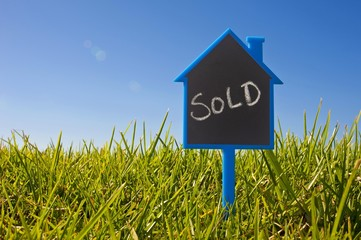 "Sign shaped like a house in the grass, lettering ""Sold"", symbolic image for purchase of building ground"