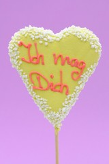 "Gingerbread heart on a stick labeled ""Ich mag Dich"", German for ""I like you"", symbolic image for love"