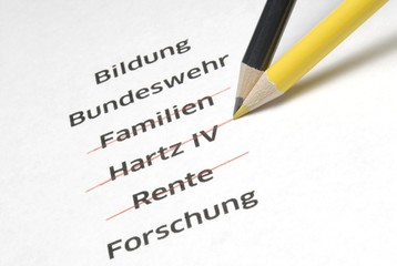"A yellow and a black pencil crossing out the letterings ""Familien"", ""Hartz IV"" and ""Rente"", German for ""families"", ""Hartz IV"", a German unemployment benefit, and ""pension"", symbolic image for the policy of economy measures of the Conservative Parties in Germany"