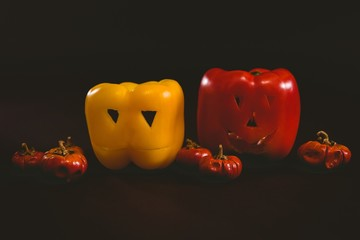 Carved bell peppers with small pumpkins over white background