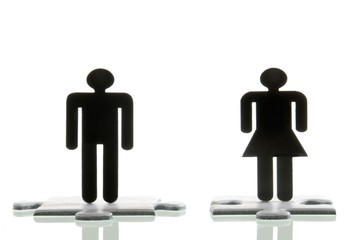 Male figure and a female figure standing on jigsaw puzzle pieces, symbolic image for looking for a partner