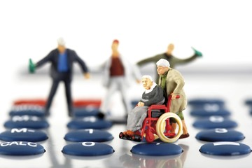 Figurine of a man in a wheelchair, blurred hooligans in the back, on a calculator