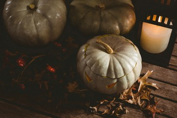White jack o lanterns with autumn leaves by candle on table