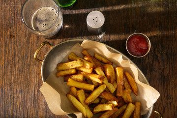 Pan of fries with ketchup and glass of dark beer