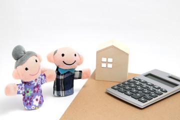 シニアの夫婦と家と計算機