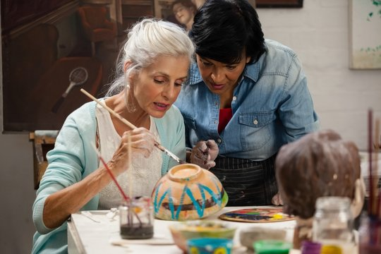 Woman assisting senior woman in painting bowl at drawing class