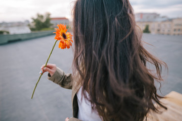 Close up picture of unrecognizable young girl with orange flower on urban city background. Meeting on roof, freedom and romantic dreams, happiness and love concept