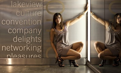 Young dark-haired woman wearing a beige dress and high heels posing in front of a wall with lighting