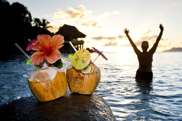 Two coconuts with cocktails and decorations on a granite rock at sunset, in the back a woman is standing in the sea, Seychelles, Indian Ocean, Africa