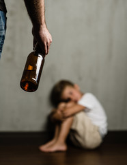 Domestic violence: father hand with a bottle of beer and frightened beaten son. Focus on hand