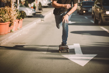 Pro skateboard rider in front of car on city street