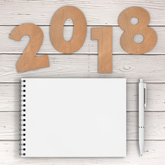 Cardstock Numbers 2018 Happy New Year Sign near White Spiral Paper Cover Notebook with Pen over table. 3d Rendering
