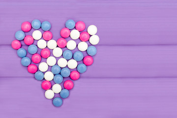 Candies of different colors forming a heart on a purple background